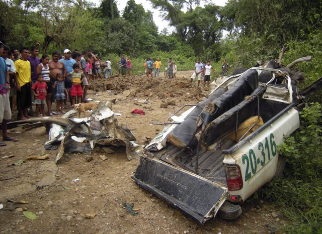 Residents look at the remains of a police car, damaged after a landmine explosio