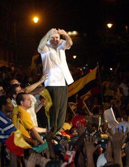 Ecuadorean former president Abdala Bucaram covers his eyes from spot lights on t