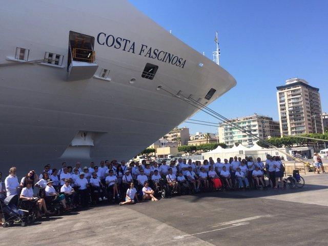 Socios y familiares de Aspaym posan junto al barco en el que harán el crucero