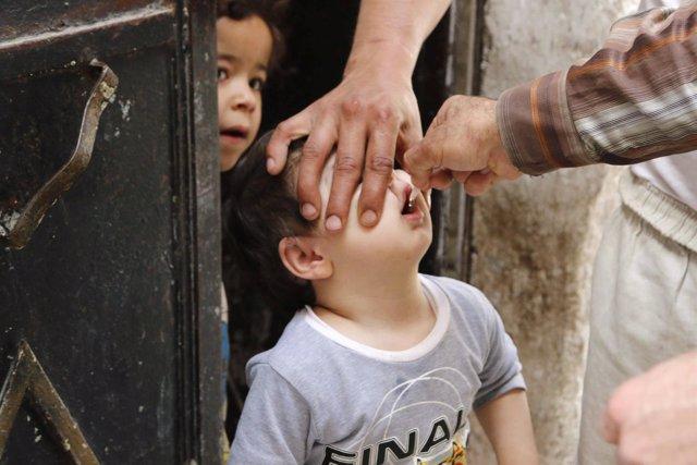 Un niño toma la vacuna contra la polio en Alepo, Siria.