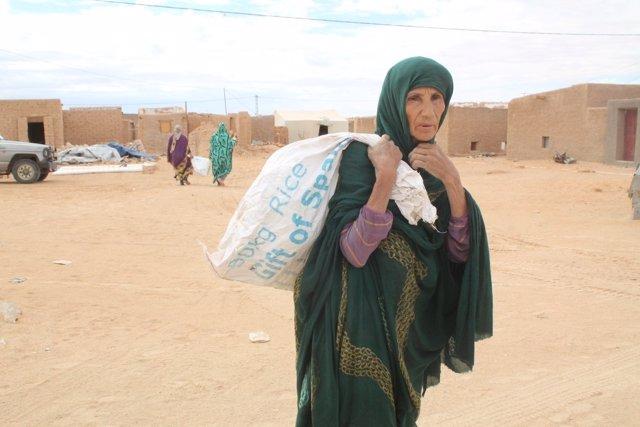 Una refugiada saharaui carga un saco con comida