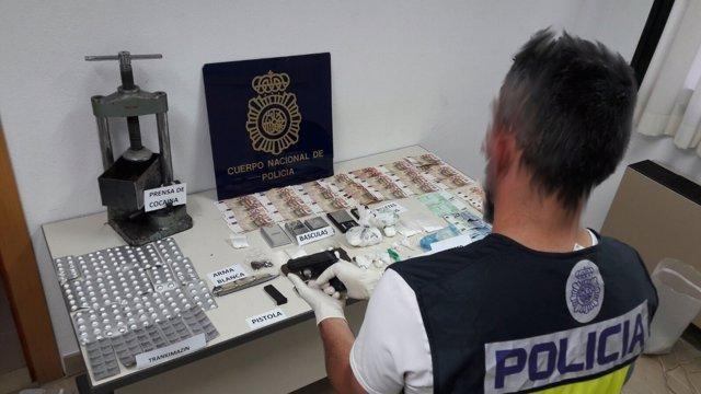 Un agente con la droga y el dinero falso localizado