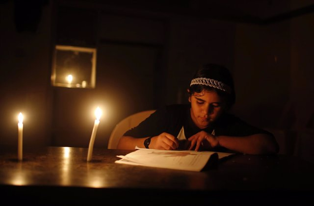 Una niña palestina hace los deberes a la luz de una vela en Gaza