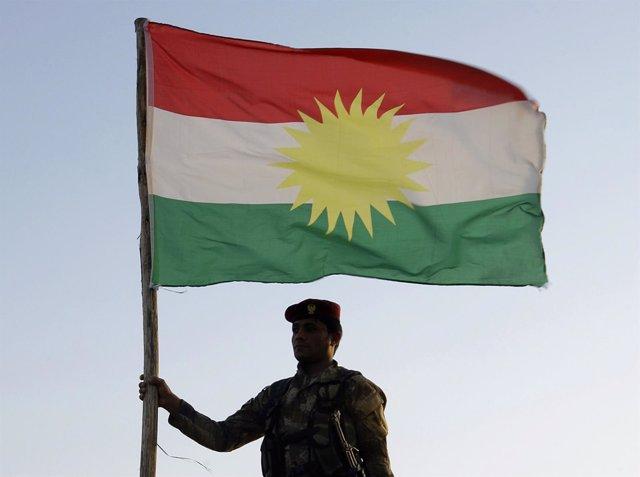 Un soldado peshmerga con una bandera del Kurdistán
