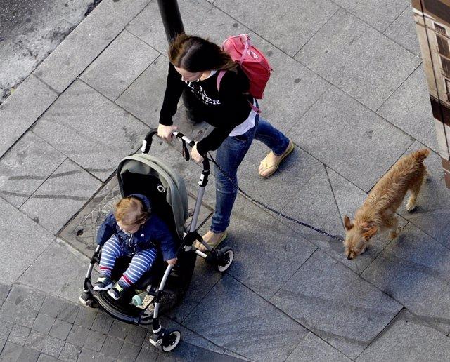 Mujer paseando en la calle, niño, niña, familia, carrito, conciliación