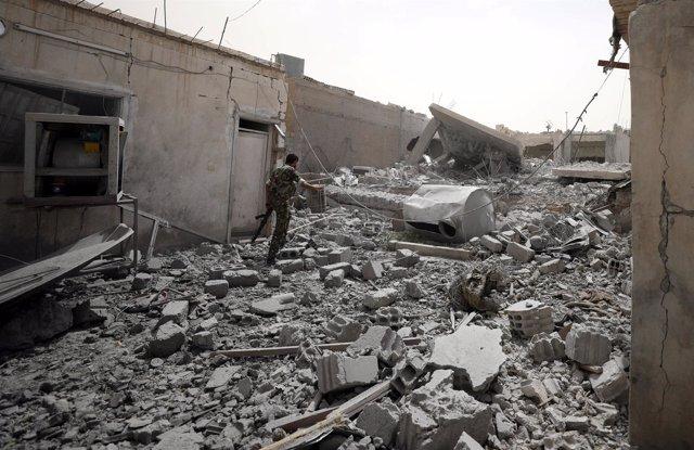 Un rebelde sirio camina entre los escombros en Raqqa