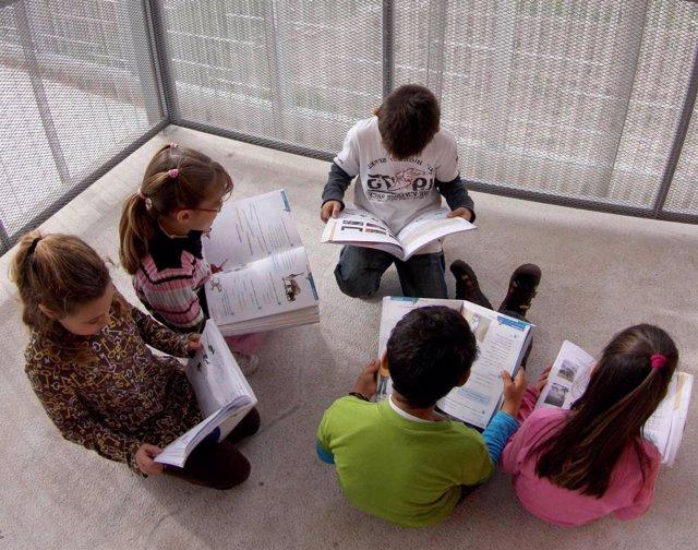 Alumnos leen sus libros de texto