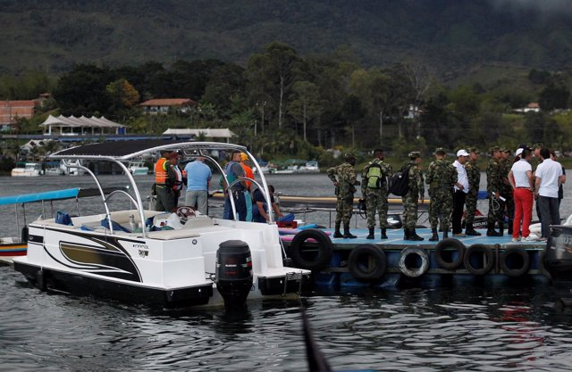 Rescuers wait at the dock after a tourist boat sank with 150 passengers onboard