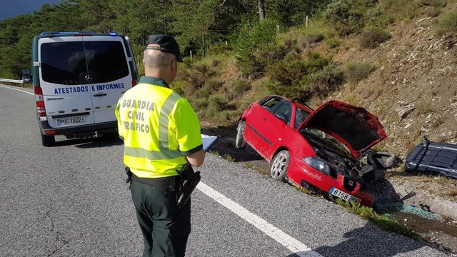 Un agente de la guardia civil junto al coche accidentado