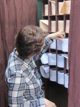 Votante seleccionando una papeleta en un colegio electoral