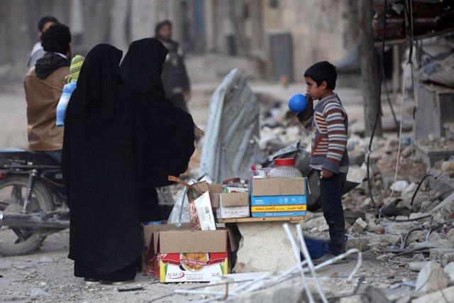 Dos mujeres compran en un puesto a un niño en Al Bab