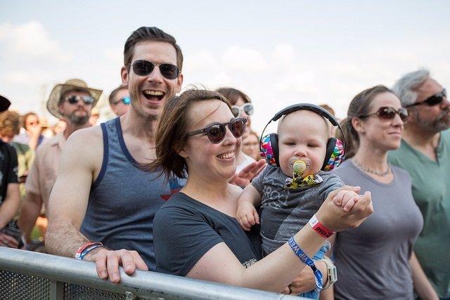 Bebé con auriculares en un concierto, familia, sonrisas