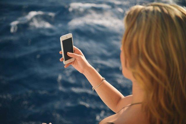 Menor usando smartphone en vacaciones