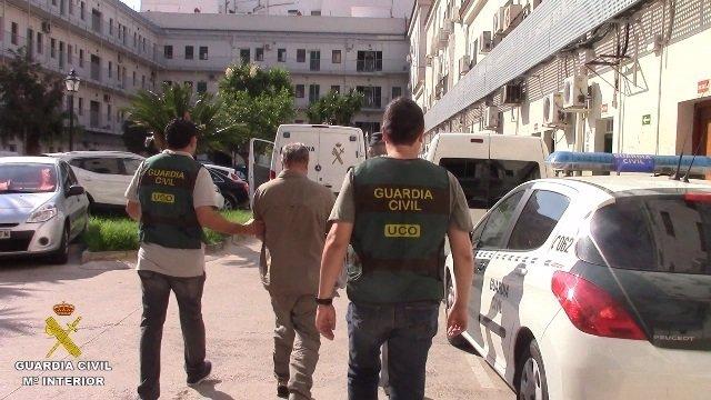 Uno de los diez detenidos custodiado por la Guardia Civil