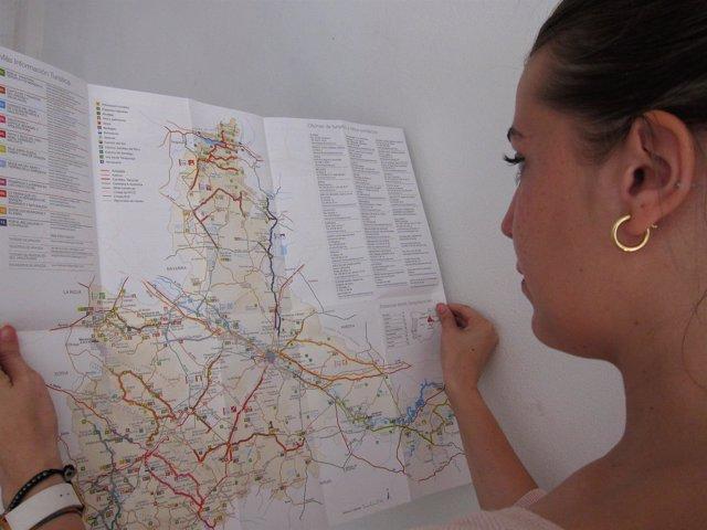 Una joven consulta un mapa turístico de la provincia de Zaragoza