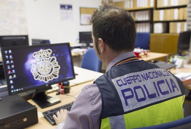 Jefe de grupo de la UDEF frente al ordenador, policía nacional, agente