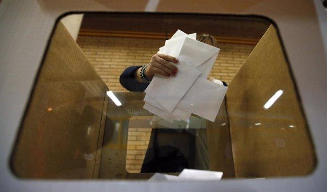 Un voluntario coge papeletas el 9 N de 2014, día del referéndum en Cataluña
