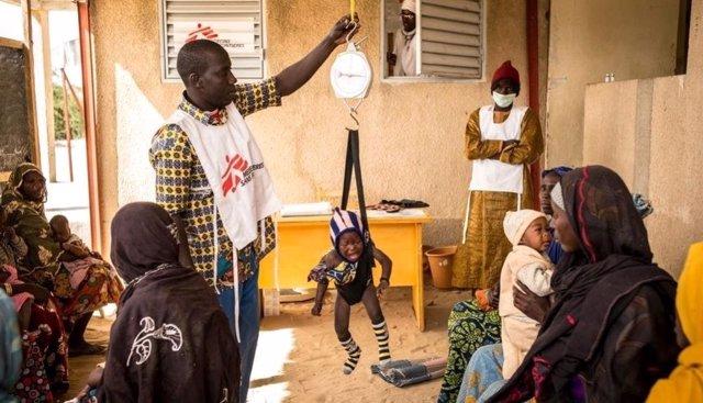 Médico tomando el peso a un niño en Níger