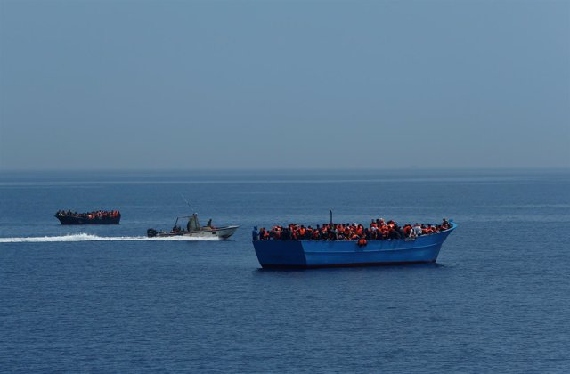 Un barco de los guardacostas libios junto a embarcaciones con inmigrantes