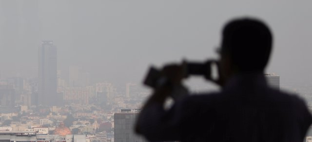 A man takes photos of buildings shrouded in smog during an environmental conting