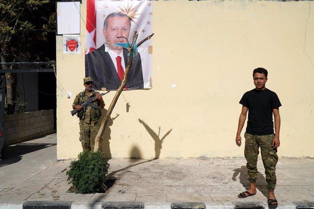 Miembro del ELS con un retrato de Erdogan en Jarablus