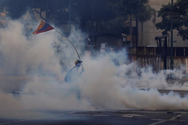 A demonstrator carrying a national flag walks away from tear gas during clashes