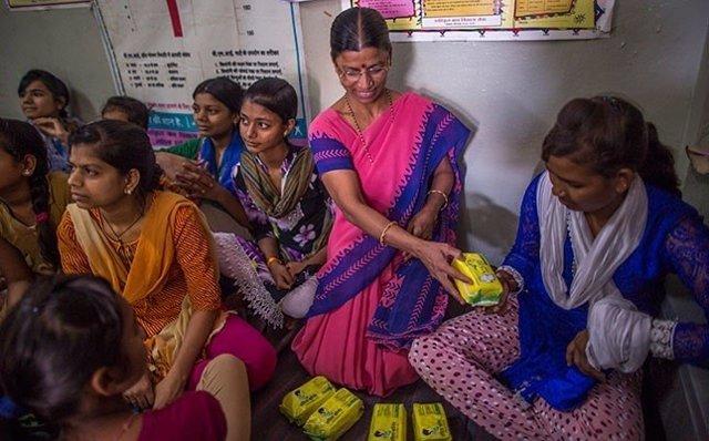 Una profesora reparte productos de higiene sanitaria entre las mujeres