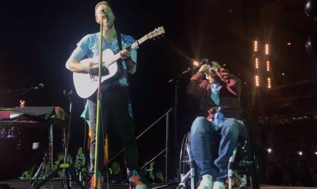 Fan de Coldplay en silla de ruedas sube al escenario a tocar con sus ídol