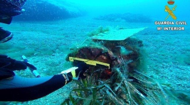 Un agente del GEAS señala a la supueta carga de profundidad