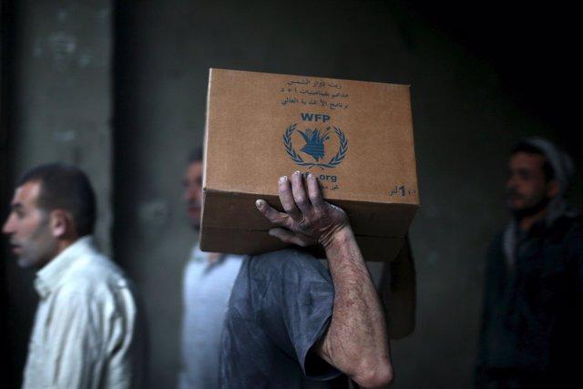 Hombre con una caja de ayuda humanitaria del PMA en Siria
