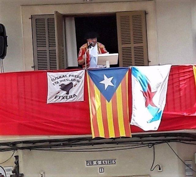 Momento del pregón de Llubí con bandera apoyo a presos de ETA