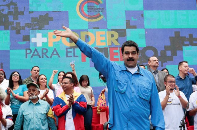 Venezuela's President Nicolas Maduro (C) waves as he arrives for an event with s