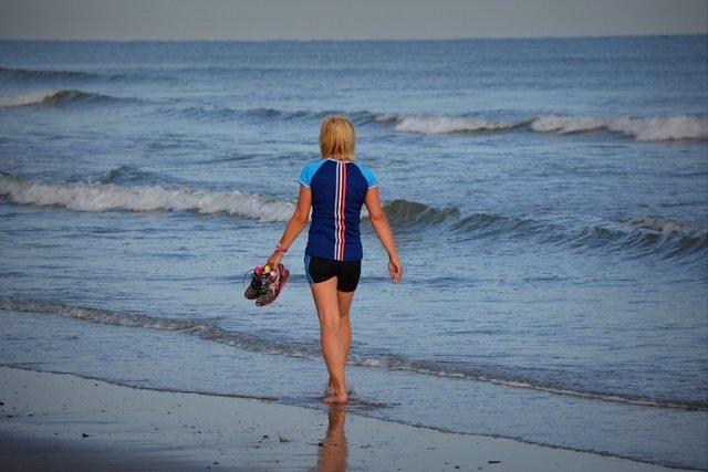 Chica andando por la playa. Deporte. Aire libre