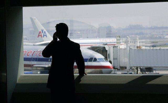 Persona hablando por teléfono en el aeropuerto con aviones de American Airlines
