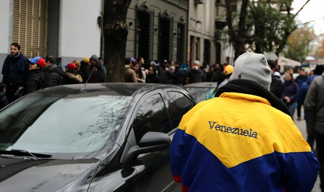A man wears a jacket with the colours of Venezuela's national flag as other Vene