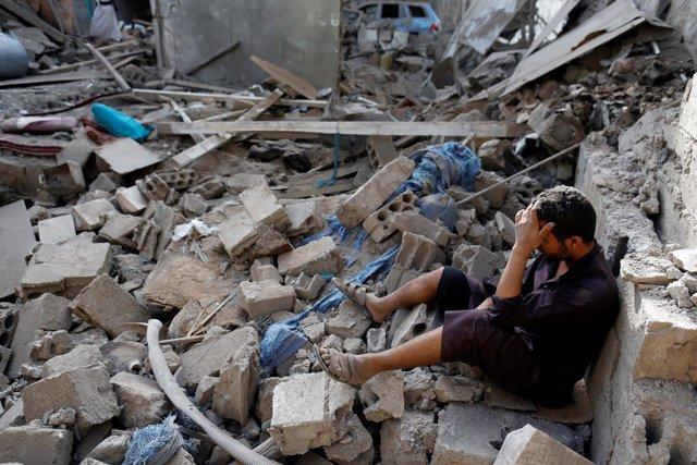 Un hombre sentado sobre los escombros de una casa en Saná