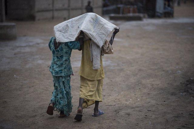 Dos personas se refugian de la lluvia en Nigeria
