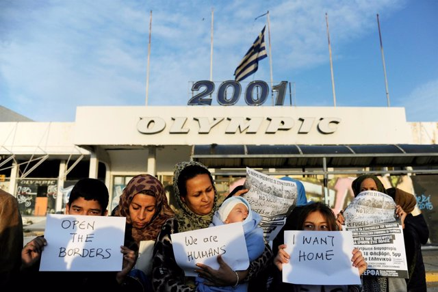 Refugiados con pancartas delante del antiguo aeropuerto de Elliniko, en Atenas