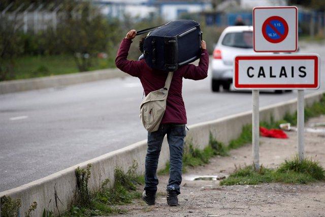 Un migrante lleva sus pertenencias en Calais