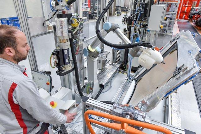 Operarios de Audi trabajan con robots