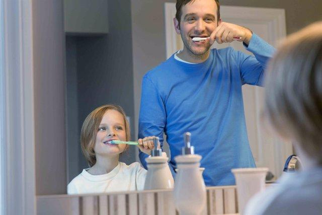 Padre y niño limpiándose los dientes. Higiene dental. Cepillarse los dientes.