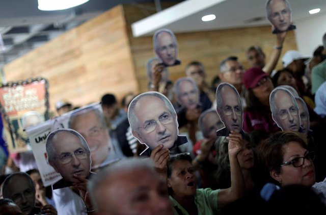 People hold portraits of opposition leader Antonio Ledezma during a news confere