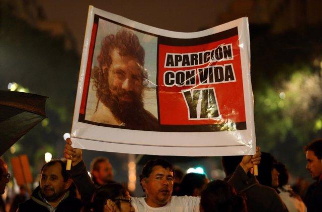 Un hombre sostiene una pancarta con la imagen de Santiago Maldonado.