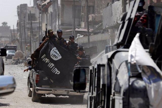 Policías iraquíes con la bandera de Estado Islámico en Mosul