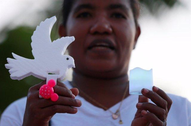 Una activista sostiene una paloma en señal de protesta contra la violencia.