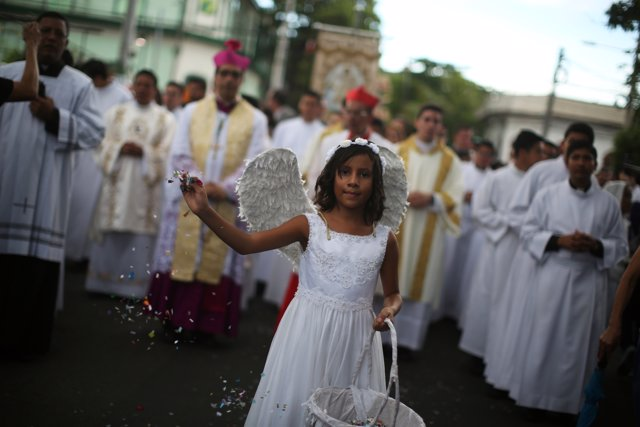 A girl throw confetti as she participates in a procession to commemorate the Fea