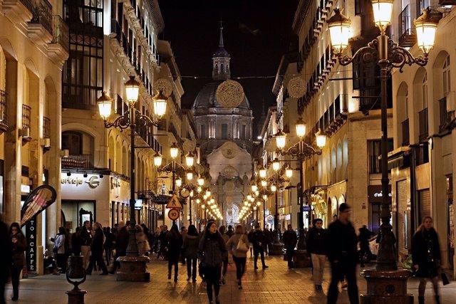 Calle iluminada. Farolas. Gente andando por la noche.