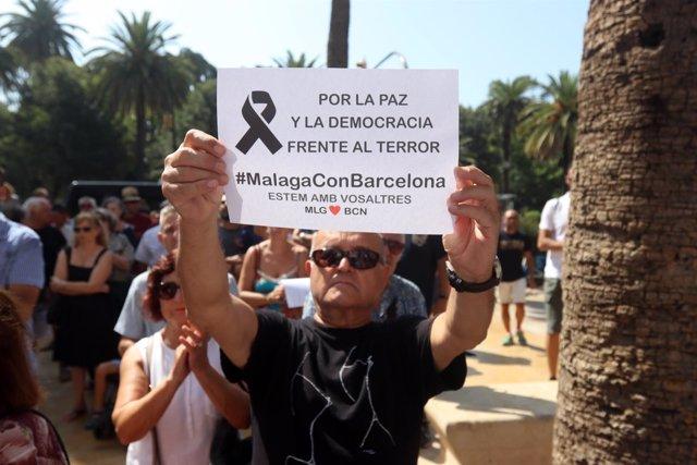 Un ciudadano porta un cartel de rechazo a los atentados en cataluña