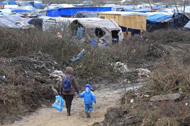 Un inmigrante y su hijo en un campamento de Calais, en una imagen de archivo