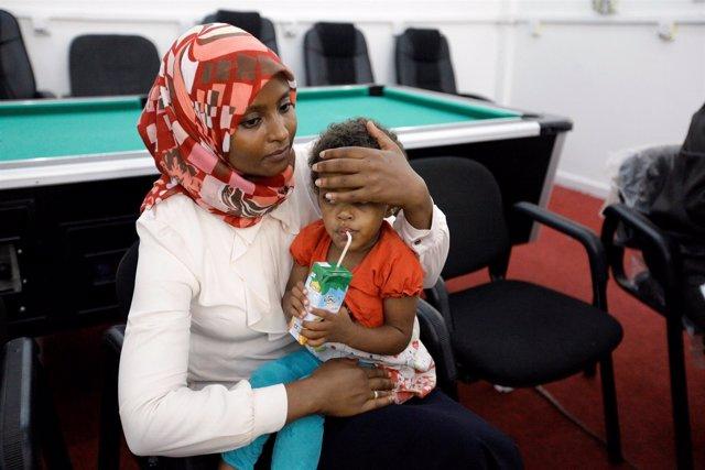 Una mujer de la Cruz Roja con un hijo de un miembro de Estado Islámico